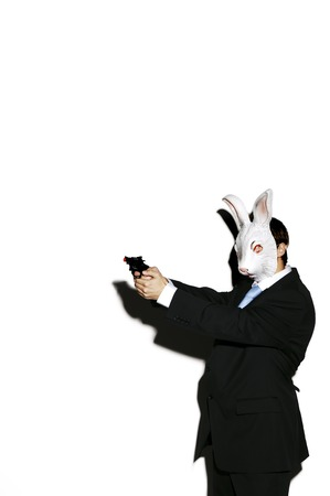 Businessman in rabbit mask aiming a pistol photo