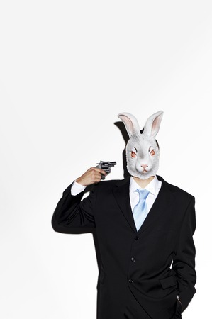 Businessman with rabbit mask pointing a pistol at himself photo