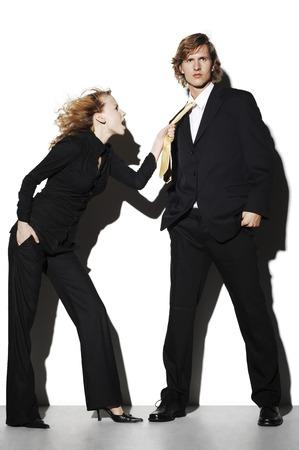 Businesswoman pulling a businessmans tie photo