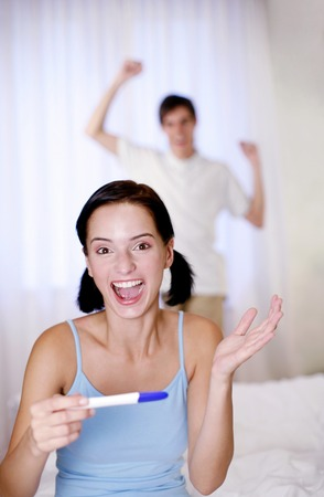 gratified: Couple jubilating after looking at the pregnancy test result