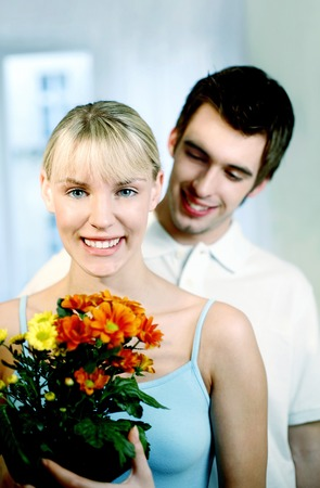 Woman looking happy to receive a bouquet of flowers from her husband