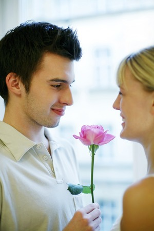 Man giving his wife a flower photo