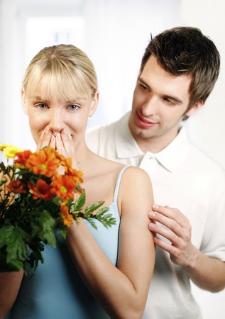 Woman looking surprised to receive a bouquet of flowers from her husband