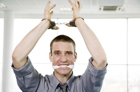 handcuffed: Zakenman met zijn handen geboeid en zijn mond wordt gevuld met een doek