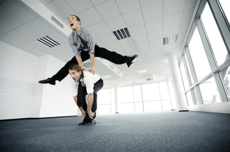 desirous: Businessman jumping over his colleague Stock Photo