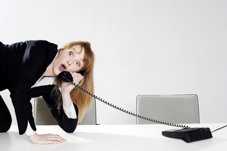 Businesswoman struggling to answer a phone call photo