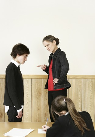 Teacher scolding her student for not completing his homework