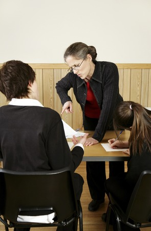 man scolding: Teacher scolding her student for not completing his homework