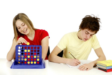 he she: Girl solving puzzle while boy is doing homework
