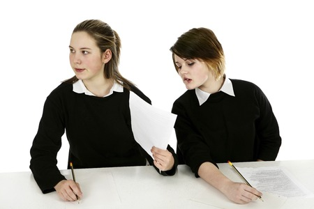 risky behavior: Girl showing her answers to her classmate