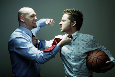 Businessmen fighting during basketball competition Stock Photo
