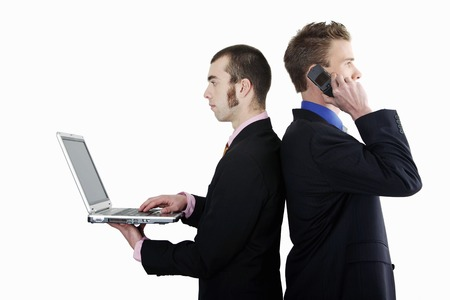 Businessmen talking on the cell phone and using laptop photo