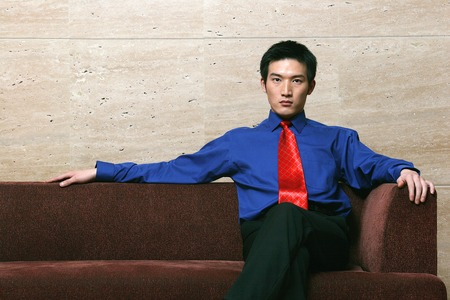 Businessman sitting on the couch with his legs crossed photo