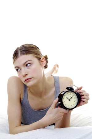 ticking away: Woman getting frustrated with her alarm clock