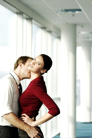 captivation: Two executives kissing in office corridor