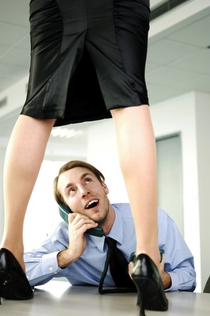 Businessman looking up at sexy woman standing on table while talking on the phone photo