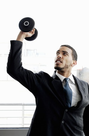 Businessman lifting dumbbell photo