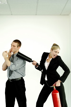 extinguishing: Businesswoman extinguishing her colleague for smoking in the office Stock Photo