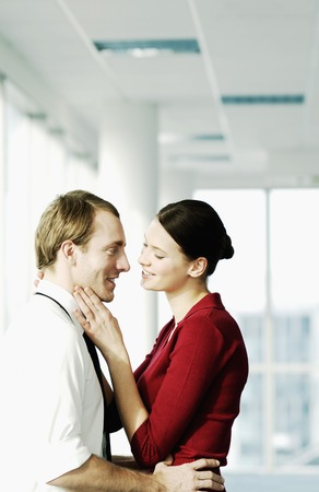 captivation: Two executives hugging in office corridor