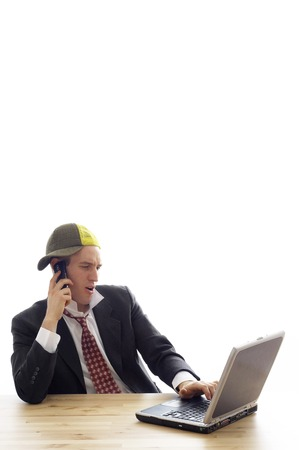 Fashionable businessman talking on the cell phone while using laptop photo