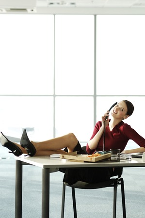 Businesswoman talking on the phone with feet up on the table photo