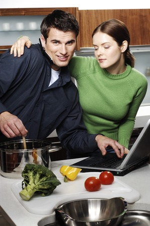 Couple using laptop while cooking in the kitchen photo