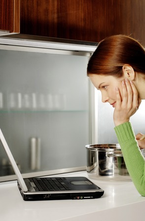 Woman using laptop while cooking in the kitchen photo