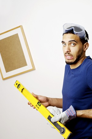 Man with goggles holding a spirit level photo