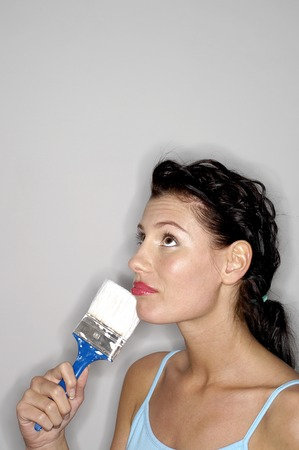 Woman holding paint brush thinking photo