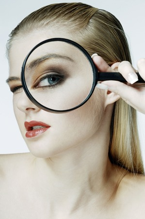 Woman using magnifying glass photo