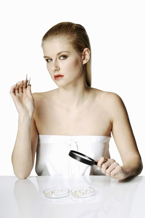 Woman holding tweezers and magnifying glass photo