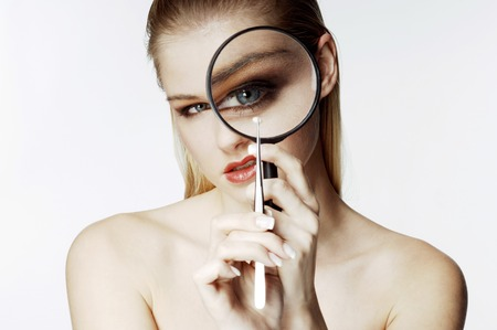 Woman looking at a tiny object with a magnifying glass photo