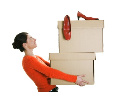 Businesswoman carrying boxes with her high heels on top