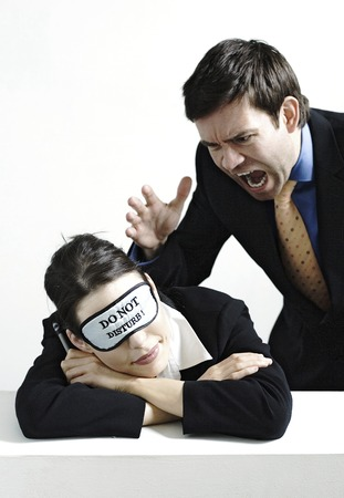 Businessman about to scream at his sleeping colleague photo