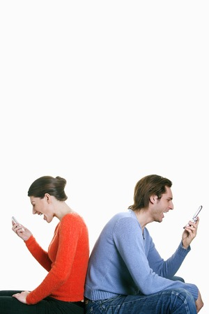 Man and woman screaming into their cell phones photo