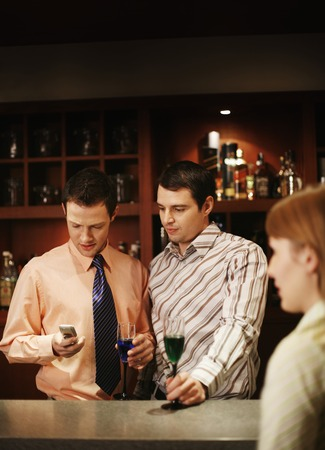 Businessman text messaging on the cell phone while drinking in the bar photo