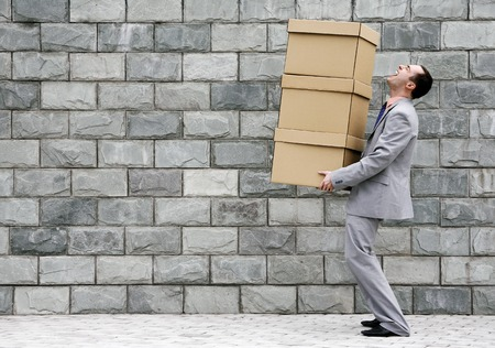 Businessman carrying a stack of boxes photo