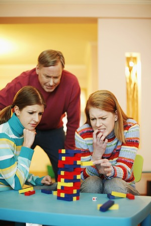 removing the risk: Family playing block game at home