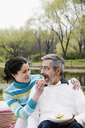Woman feeding her husband while picnicking in the park photo