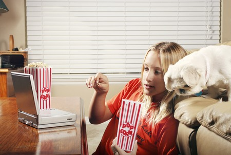 watching movie: Girl eating popcorn while watching movie on the portable DVD player Stock Photo