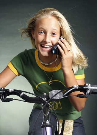 Girl talking on the mobile phone while cycling photo