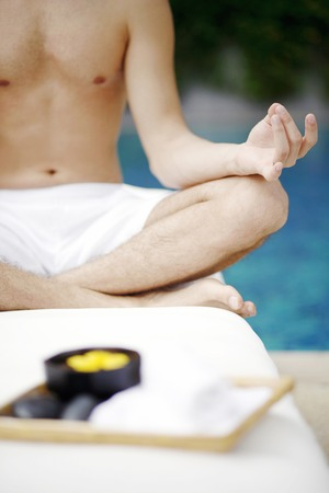 recovery position: Man meditating by the pool side Stock Photo