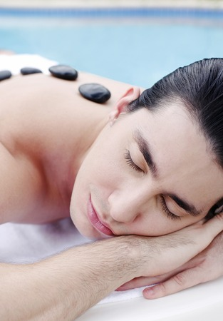 Man lying forward with therapeutic hot stones on his back photo
