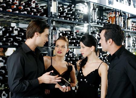tomando refresco: Dos parejas elegir el vino en la bodega Foto de archivo