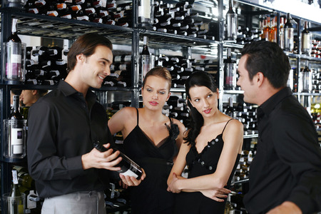 Two couples choosing wine in the wine cellar photo