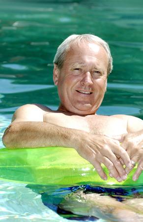 プールに浮かんでいる男 写真素材