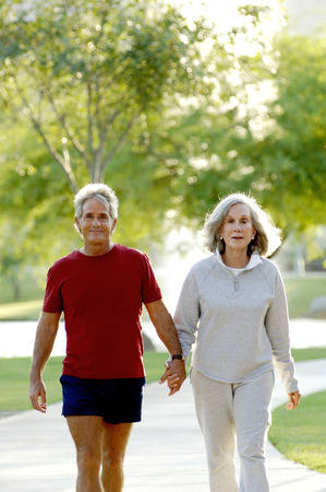 Old couple holding hands while walking in the park photo