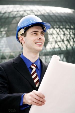 Engineer with safety helmet holding a plan photo