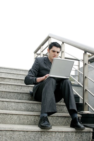 Businessman sitting on the stairs using laptop photo