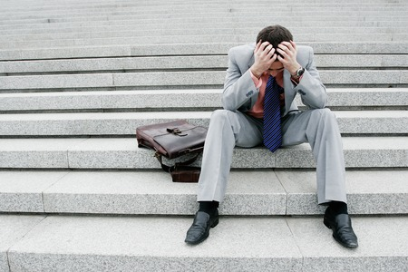 Depressed businessman sitting on the stairs Stock Photo